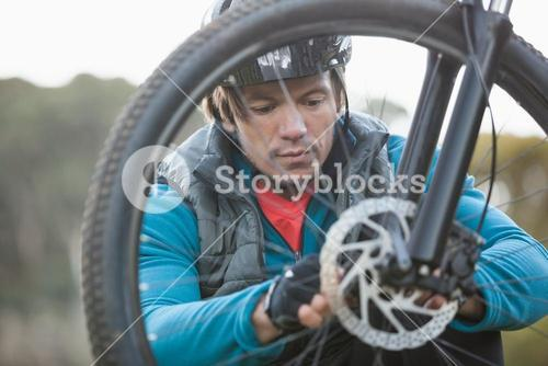 Male mountain biker examining front wheel of his bicycle