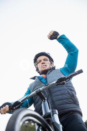 Excited male mountain biker in forest