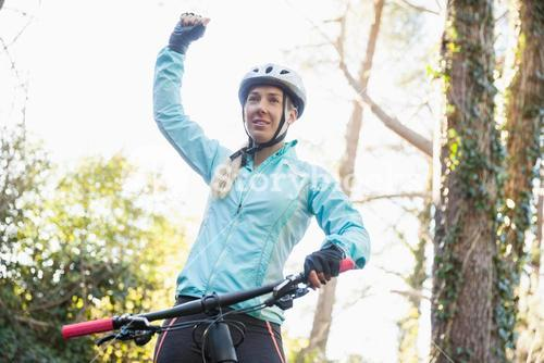 Excited female mountain biker in forest