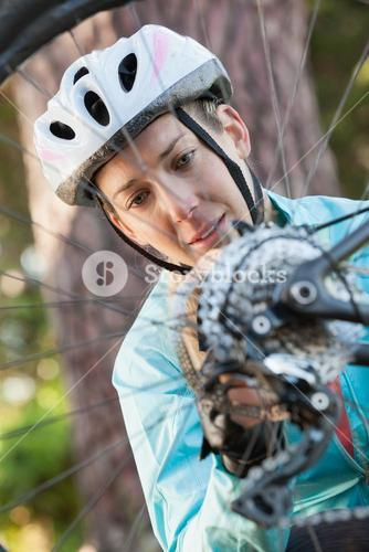 Female mountain biker examining wheel of her bicycle