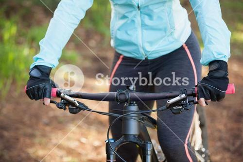 Mid section of female mountain biker riding bicycle in the forest
