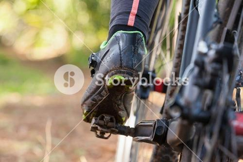 Low section of mountain biker riding bicycle