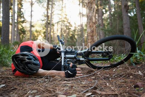 Male mountain biker fallen from his bicycle in the forest