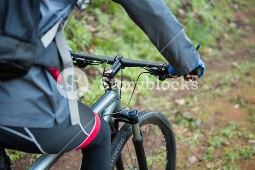 Mid section of male mountain biker riding