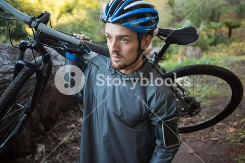 Male mountain biker carrying bicycle in the forest