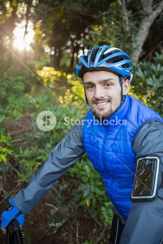 Portrait of male mountain biker with bicycle in the forest