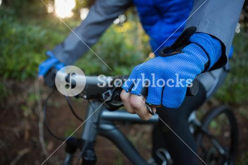Mid section of male mountain biker riding bicycle