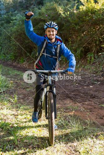 Portrait of excited male mountain biker in the forest