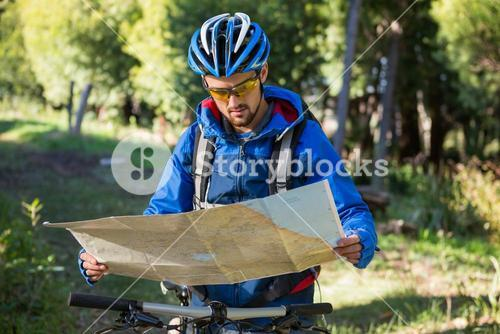 Male mountain biker looking at map