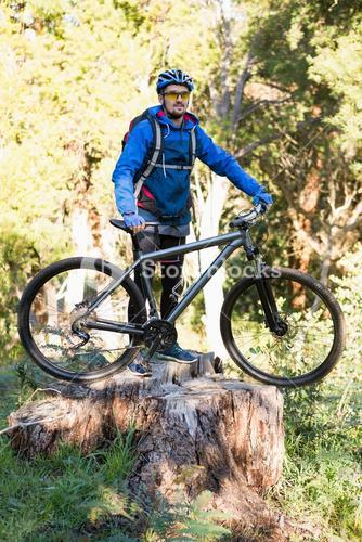 Male mountain biker standing on tree stump with bicycle