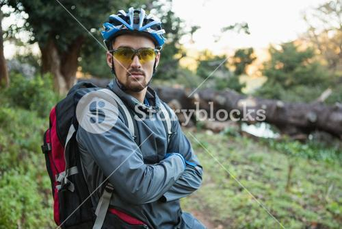 Portrait of male mountain biker with arms crossed in the forest