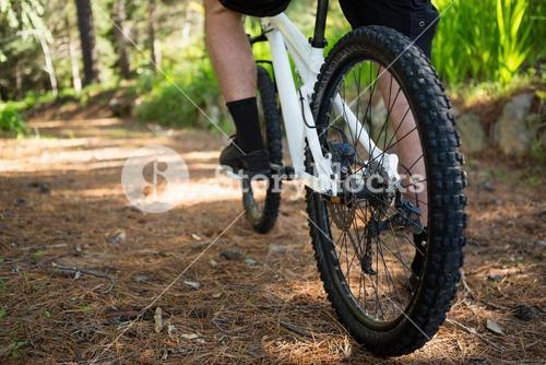 Low section of male mountain biker riding bicycle