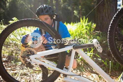 Male mountain biker fixing his bike chain