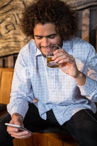 Man using mobile phone while having whisky