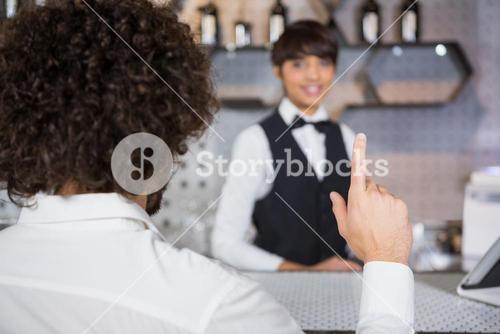 Man ordering a drink at bar counter