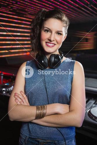 Pretty female DJ standing with arms crossed