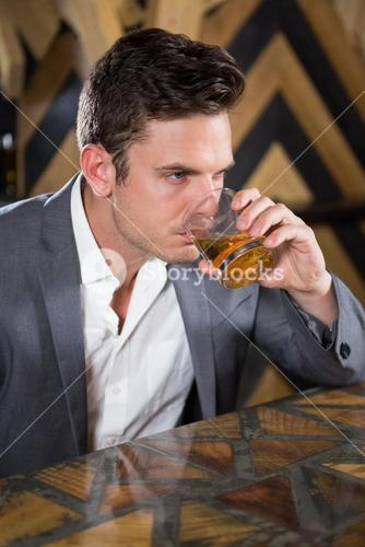 Depressed man having glass of whisky at counter