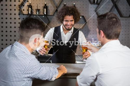 Bartender serving beer to customers