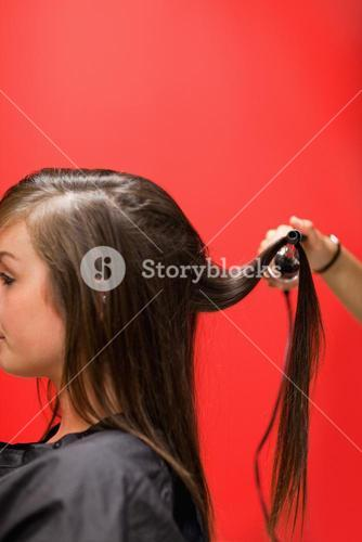 Portrait of a woman having her hair straightened