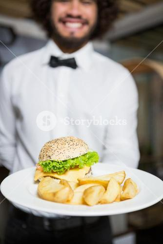 Waiter holding plates of potato chip and burger in bar