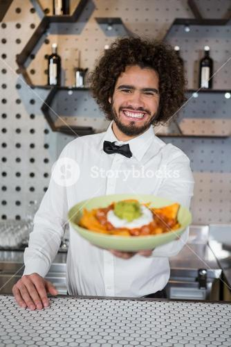 Waiter serving bowl of snack in bar counter