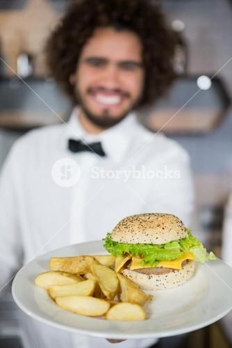Waiter serving plates of potato chip and burger in bar