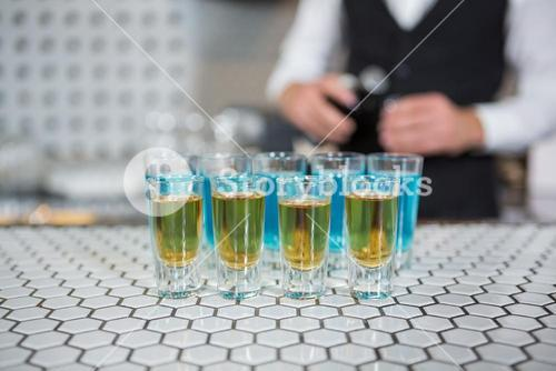 Glass of blue lagoon drinks and whisky on bar counter
