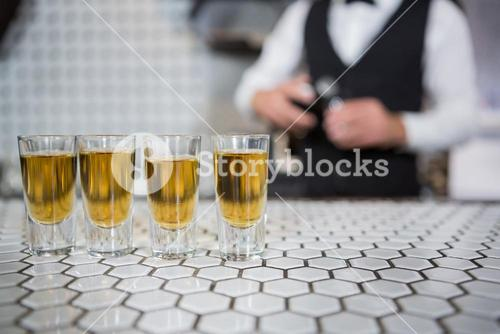 Glasses of whisky on bar counter
