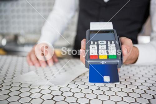 Bartender accepting a credit card at bar counter