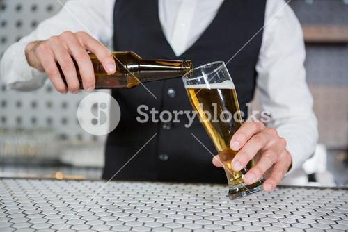 Bartender pouring beer on glass