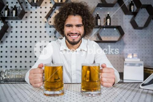 Bartender holding two glass of beer in bar counter