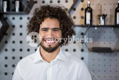 Smiling bartender standing in bar counter