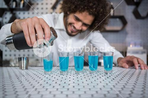 Bartender pouring cocktail into shot glasses