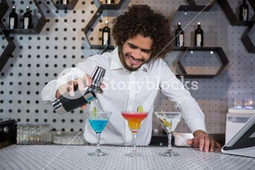 Bartender pouring cocktail into glasses