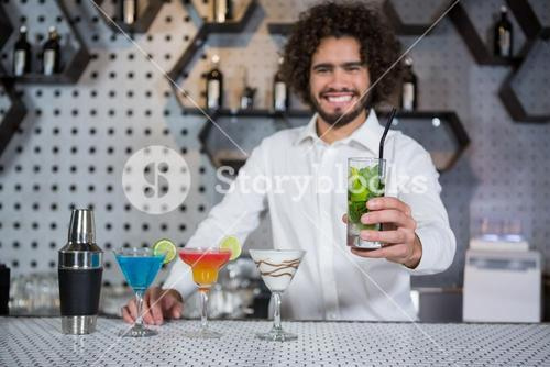 Bartender serving glass of gin