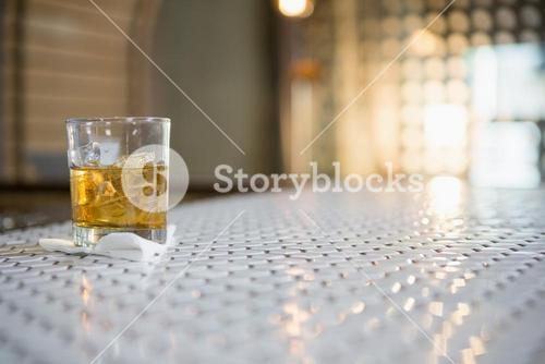Glass of whisky with ice cube on bar counter