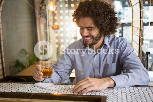 Man having glass of whisky in bar counter