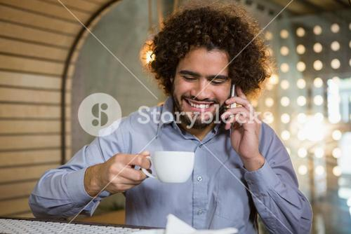 Man talking on mobile phone while having cup of tea