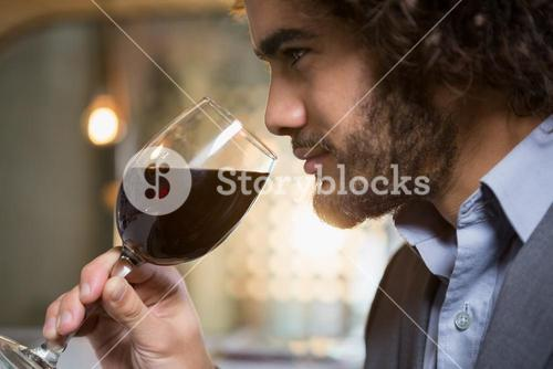 Businessman having glass of red wine
