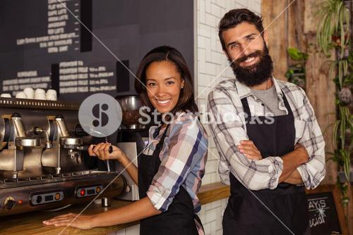 Waiter and waitress standing in kitchen