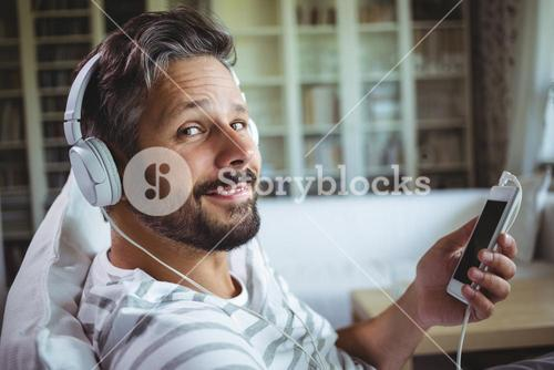 Smiling man listening to music on headphones