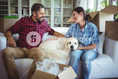 Couple sitting on sofa with their pet dog