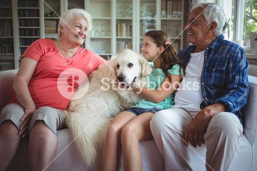 Grandparents and granddaughter sitting on sofa with pet dog
