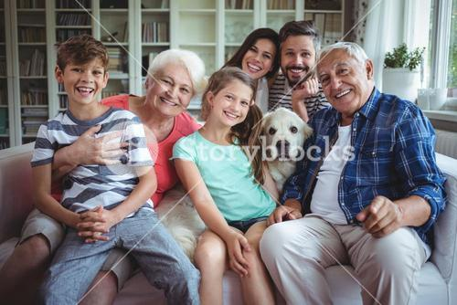 Portrait of happy multi-generation family sitting on sofa in living room