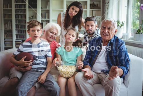 Unhappy multi-generation family watching soccer match on television in living room