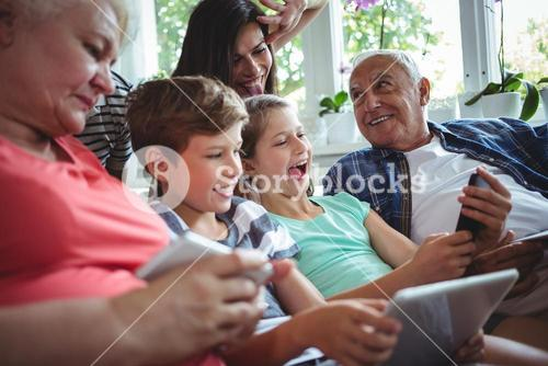 Happy multi-generation family sitting together in living room