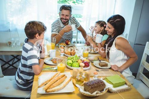 Happy family talking to each other while having breakfast together