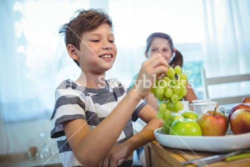 Smiling boy holding a bunch of grapes