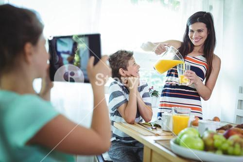 Girl clicking a photo of mother and brother from digital tablet