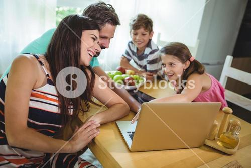 Family using  laptop at dinning table
